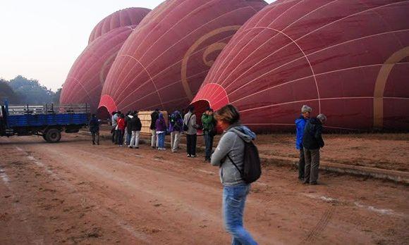 Touristen warten, währen die Heißluftballons in Bagan vor dem Abflug vorbereitet werden