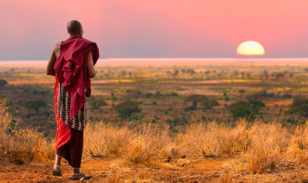 Masai warrior looks out over Serengeti at sunset, Africa, shutterstock_142942633