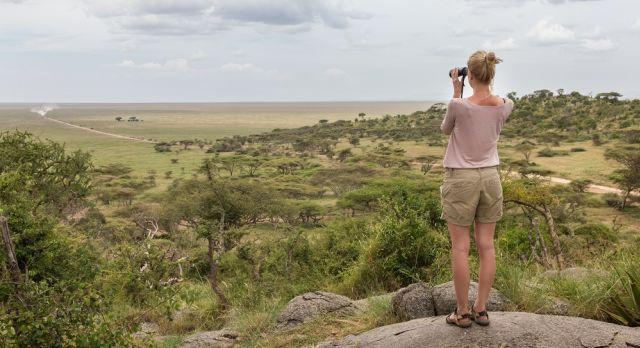 Enchanting Travels African safari parks to see - Female tourist looking through binoculars on African safari in Serengeti national park, Tanzania, Afrika.