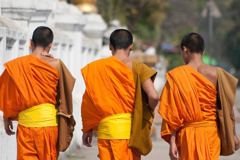 Rückansicht von drei jungen Mönchen in orangefarbener Tracht in Laos, Südostasien