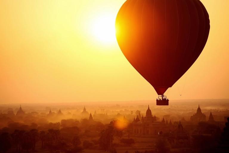 Heißluftballon schwebt bei Sonnenaufgang über den Tempeln und Pagoden von Bagan, Myanmar