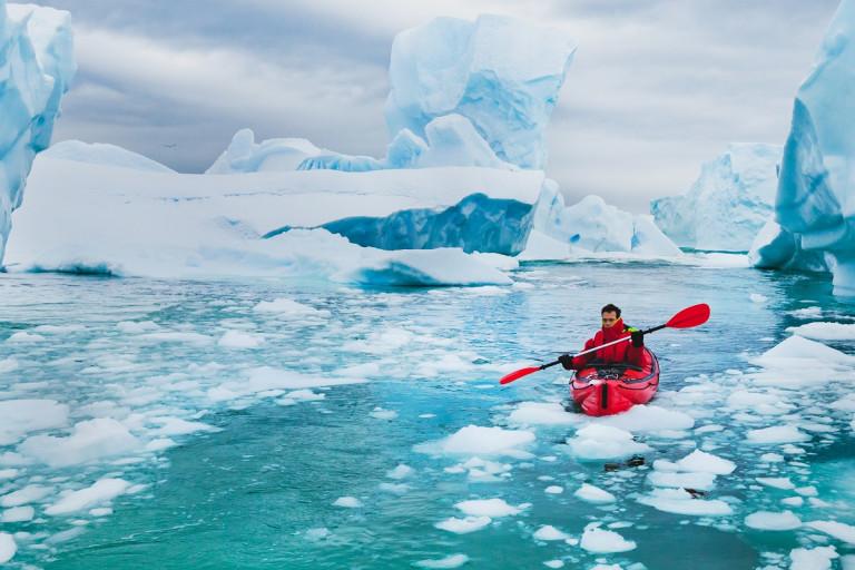 Mann fährt im Kajak durch die Eisberge der Antarktis