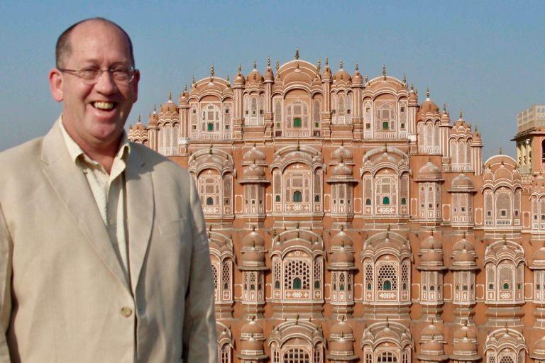 Lachender Tourist vor dem Hawa Mahal (Palast der Winde) in Jaipur, Indien