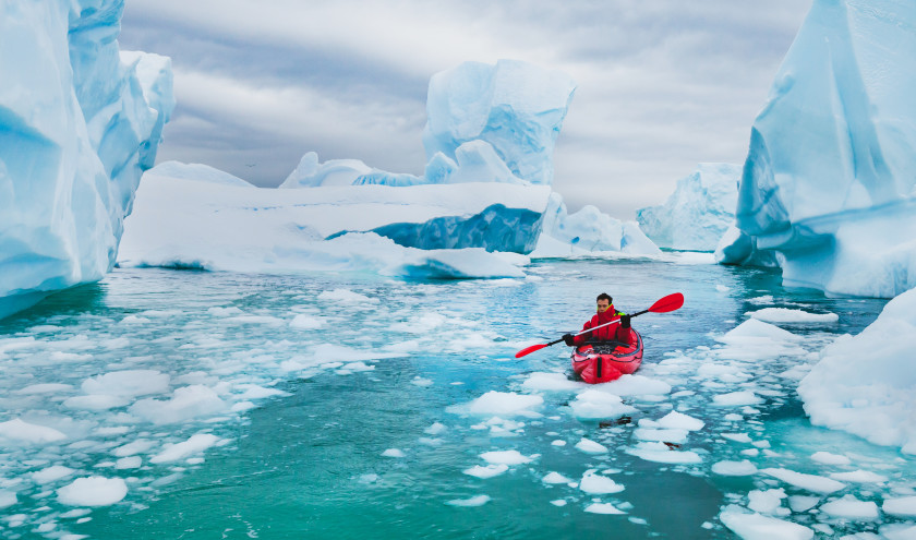 Man paddling on kayak between ice in Antractica, near Pleneau Island