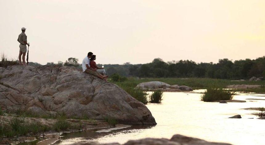 Urlaubergruppe auf Uferfelsen im Hotel Kirkman's Camp, Kruger, Südafrika