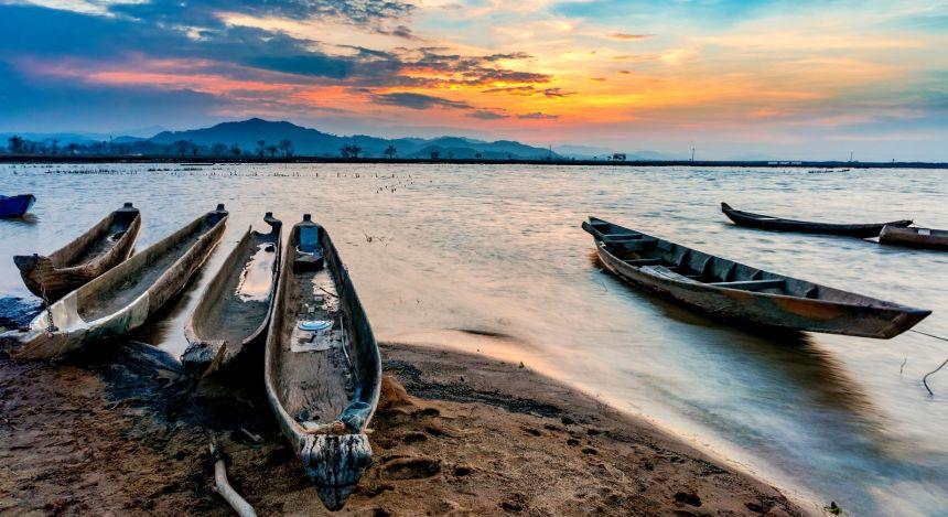 Boote liegen am Ufer bei Sonnenuntergang