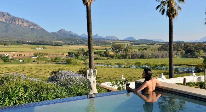 Frau im Pool überblickt weite Landschaft