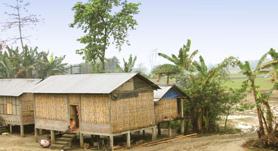 Häuser auf Stelzen vor Baumlandschaft