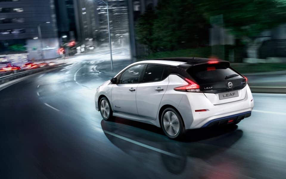 Hvit Nissan Leaf kjører i mørket i bymiljø