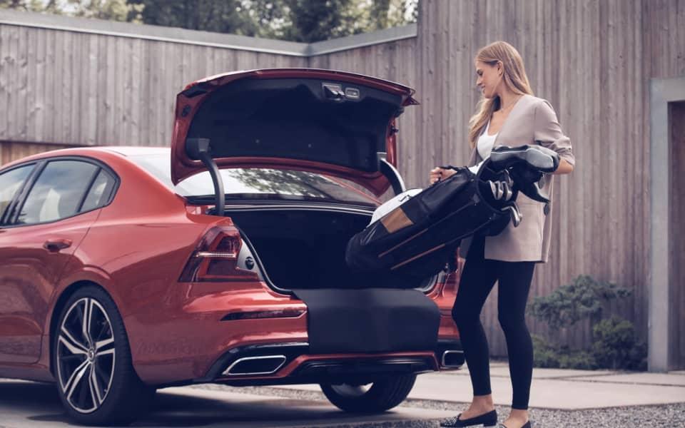 Bildet viser en kvinne som pakker en golfbag inn i bagasjerommet på en Volvo