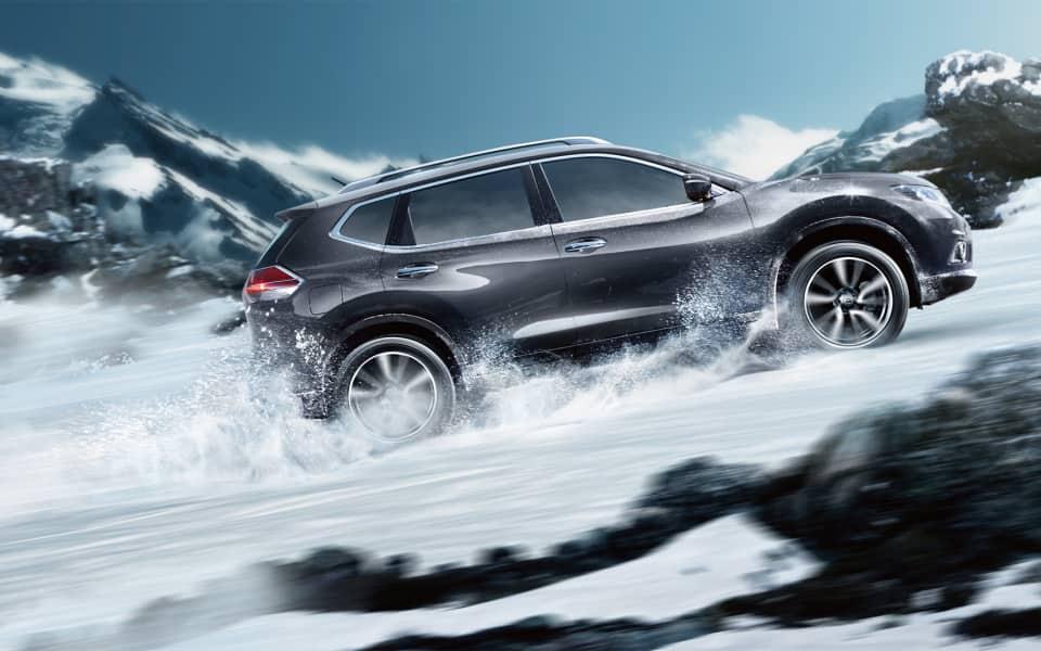 Nissan X-Trail kjører opp gjennom snøen i fjellet