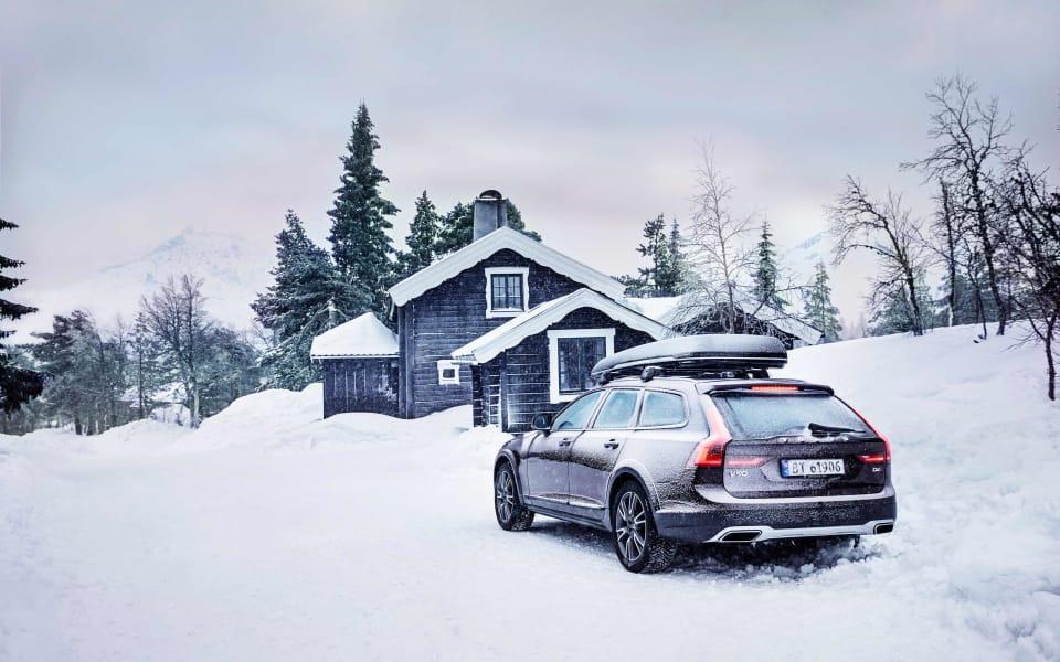 Volvo V90 Cross Country står parkert utenfor en hytte i snøen. Den har gode vinterdekk på for å kjøre på den glatte snøen.
