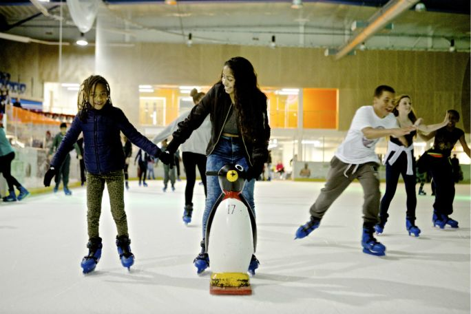 Parent ice skating with her child