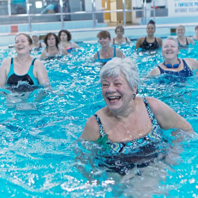 Older lady doing a water workout class with a smile on her face