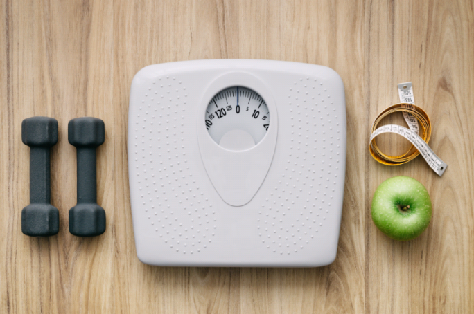 A scale, weights and apple