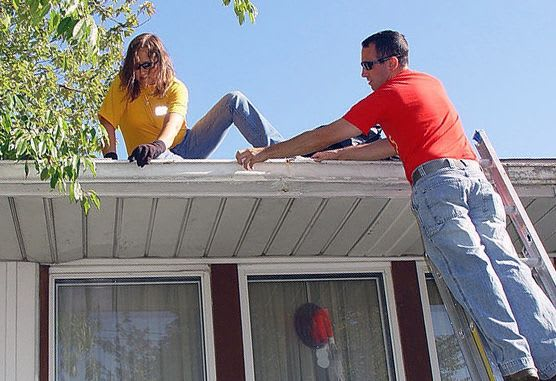 Man on a ladder and woman on roof of house, either installing or cleaning the gutters