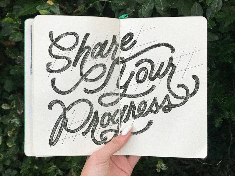 "A notebook open in someone's hand, upon which is written, ""Share Your Progress"""