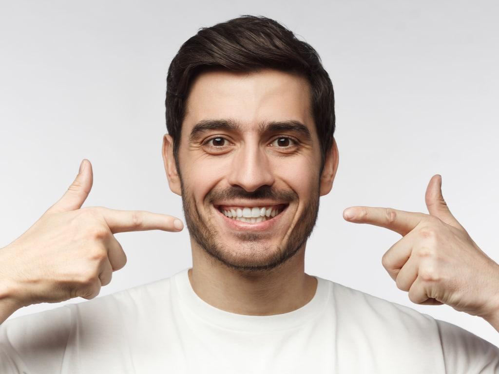 homme brun pointant son sourire avec ses doigts