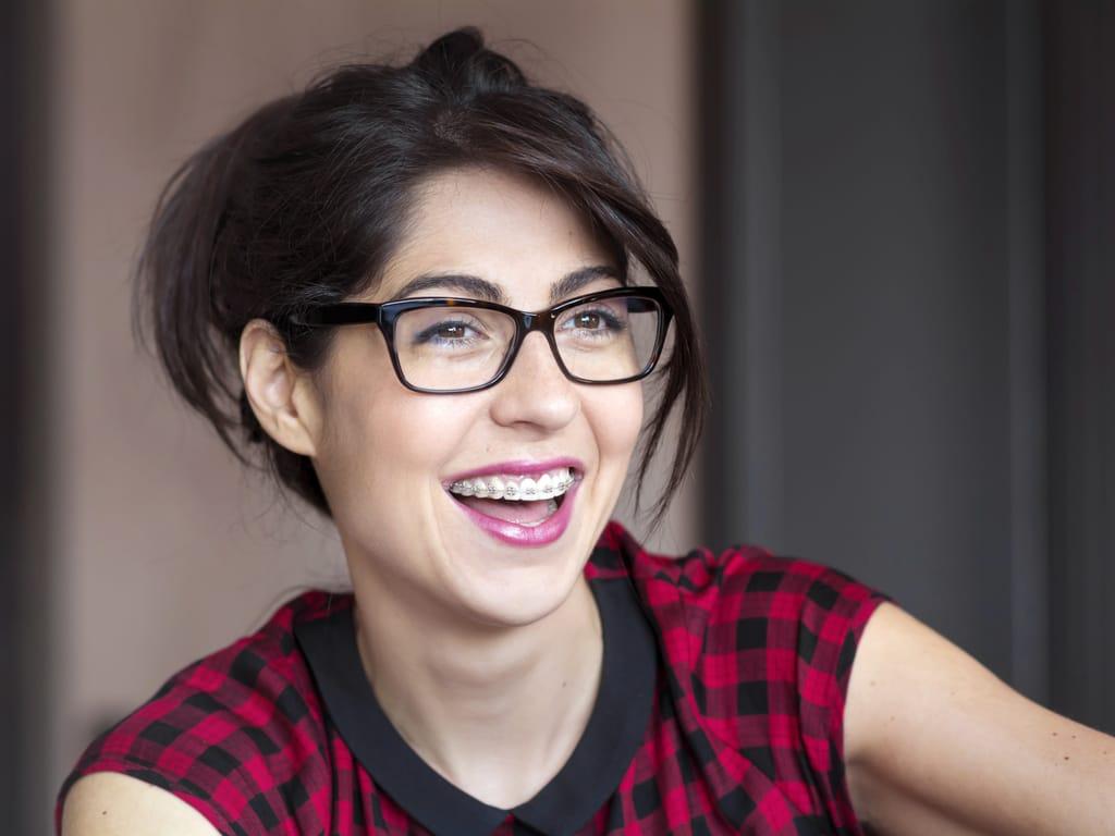 femme adulte souriante avec des bagues dentaires