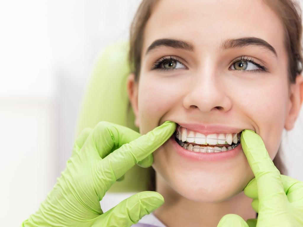 femme avec appareil dentaire et mains de dentiste avec gants verts
