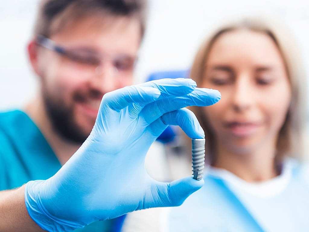 dentiste_montrant_un_implant_a_une_patiente