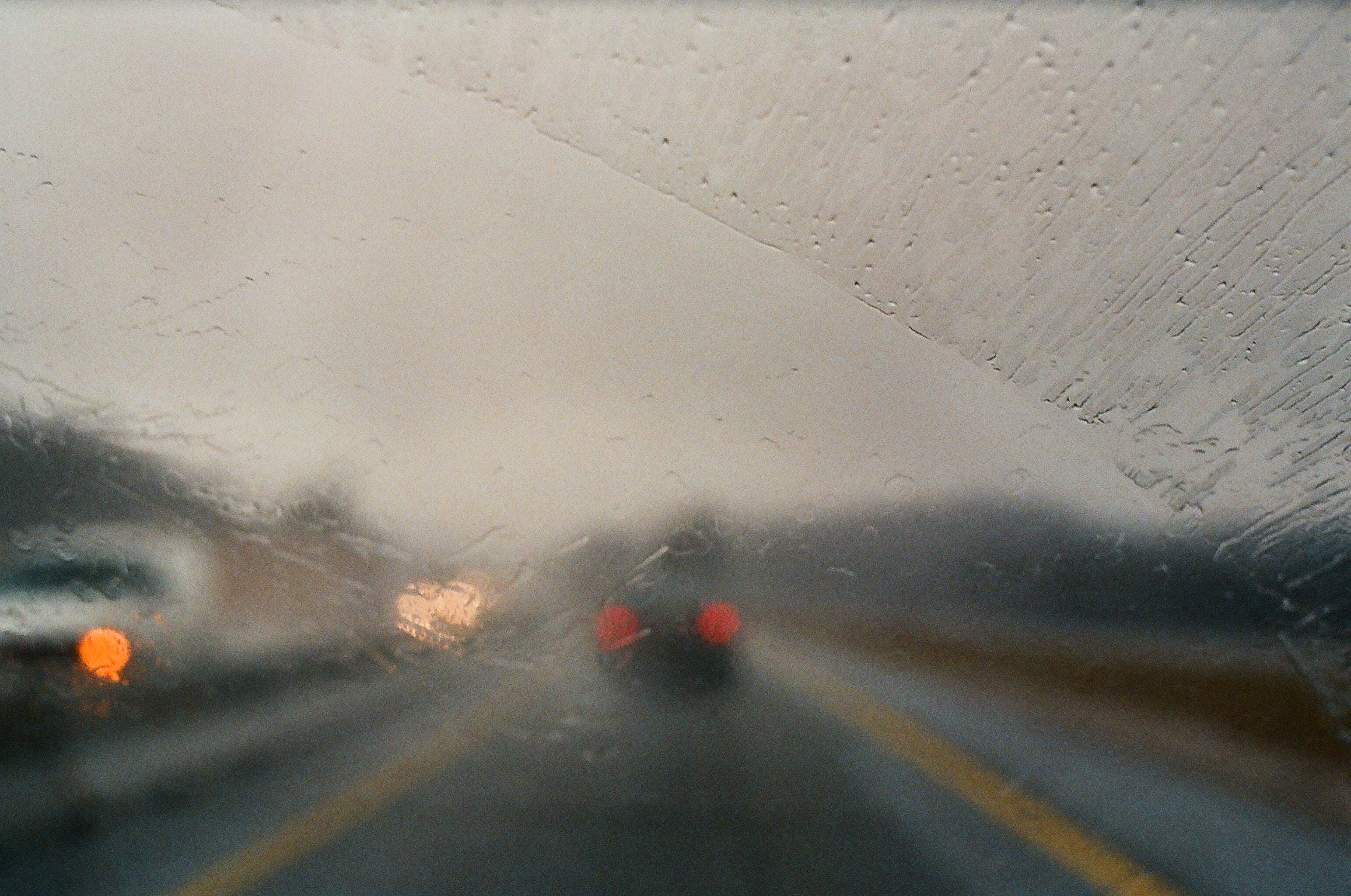 Car taillights through a blurry wet windshield during a rainstorm.