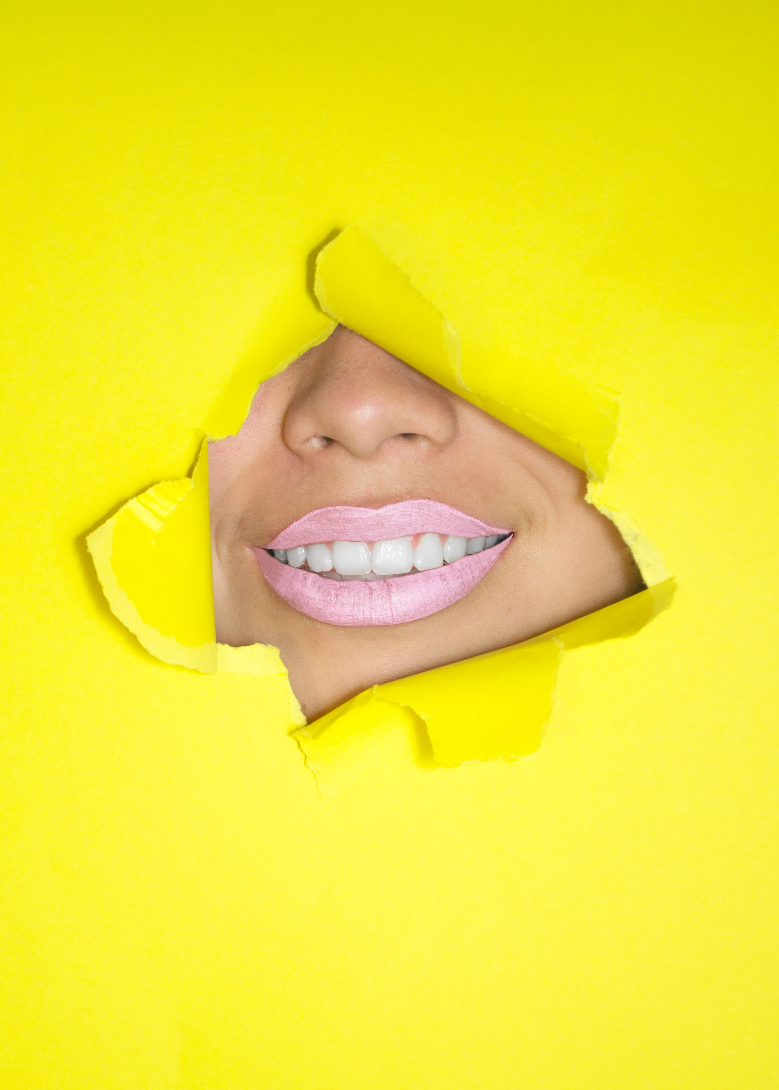 yellow background with mouth in middle woman smiling