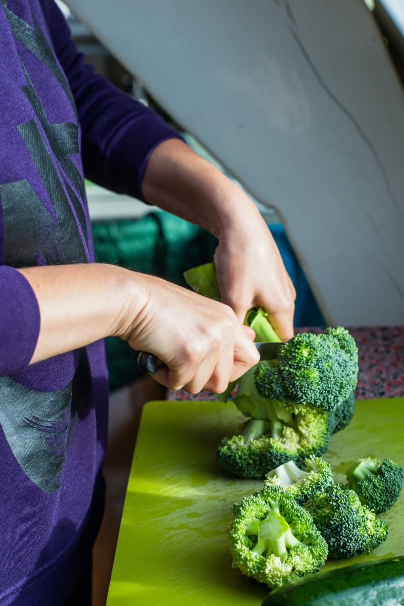 person cutting off broccoli florets from head of broccoli on green cutting board
