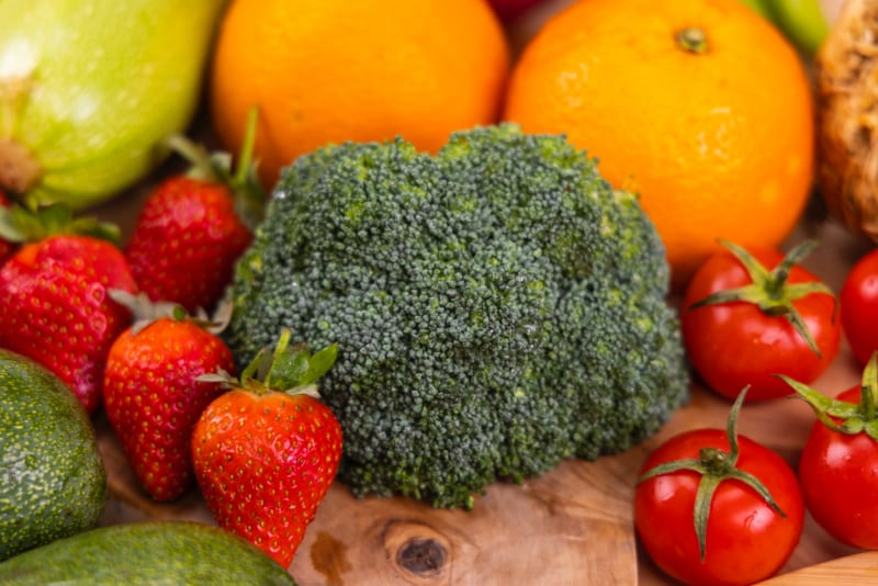 broccoli, strawberries, tomatoes, oranges on a wood cutting board