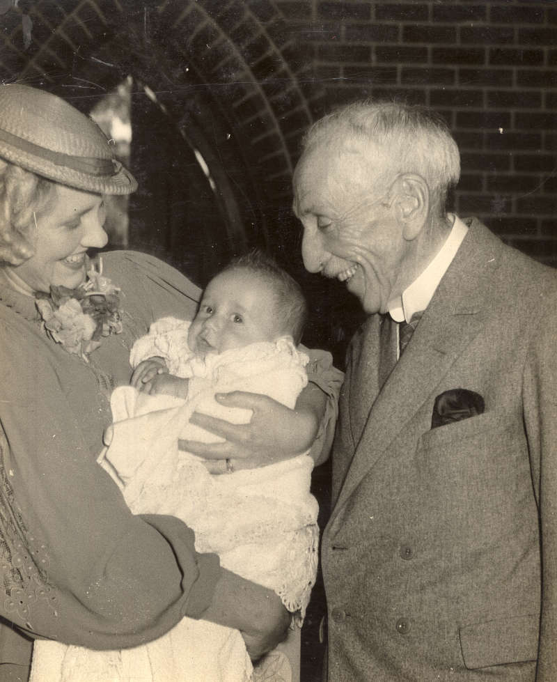 Black and white photo of Billy Hughes smiling at a woman and baby.