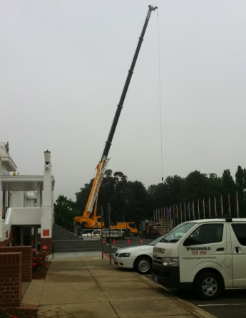 A crane carefully lifts the scaffolding on to the roof