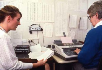 Hansard Reporter Lucy Todesco dictates her shorthand to Lyle Horgan, Typist Supervisor, in a typists' cubicle, 1988. Photograph by Robert MacFarlane, Department of the House of Representatives.  Museum of Australian Democracy Collection.