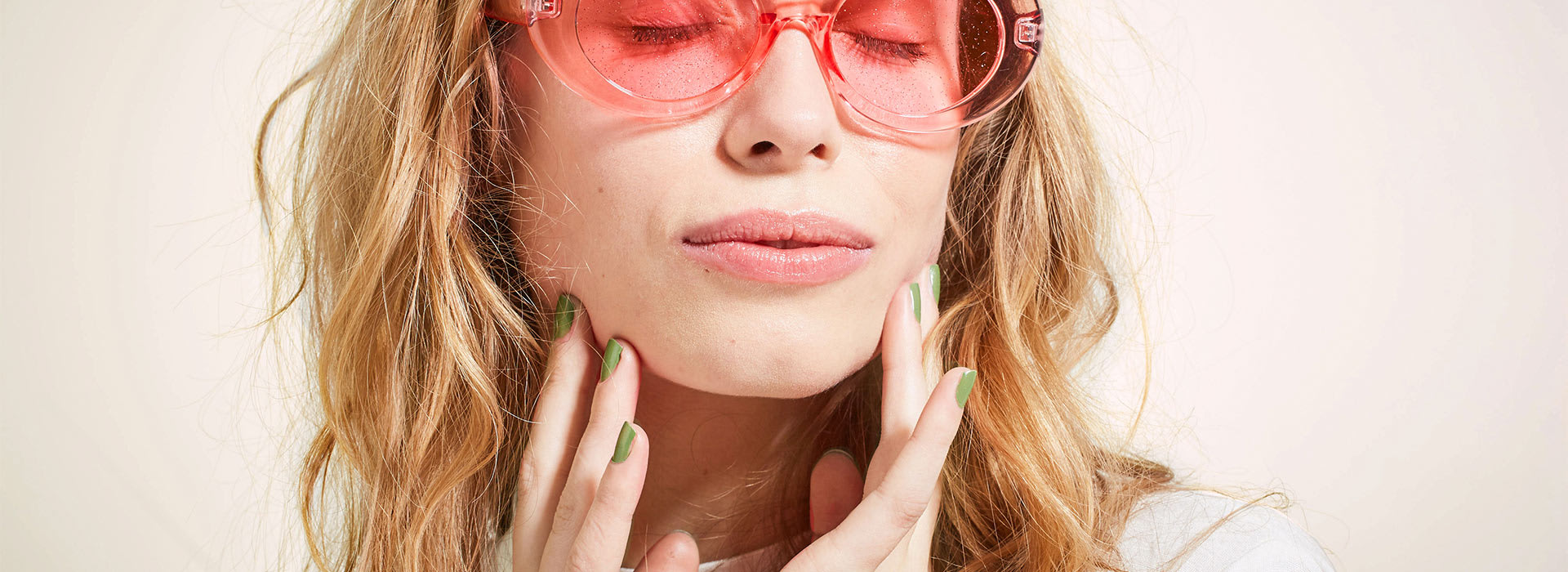 Woman in sunglasses touching her face