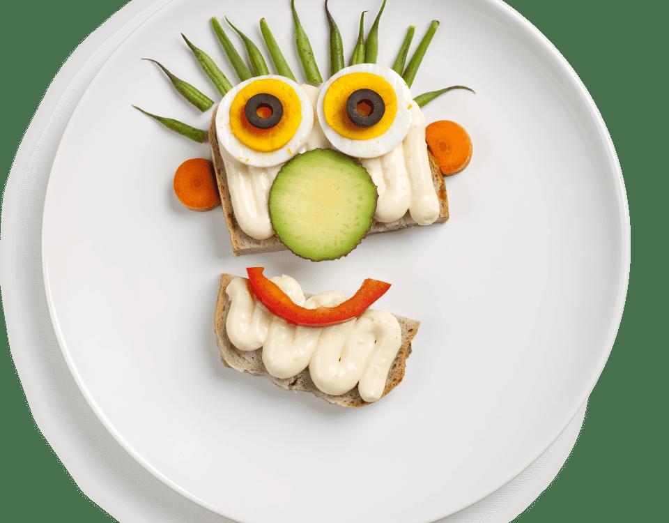 En brødskive med Kavli smøreost kan fort bli en lek hvis du lager gøye ansikter eller motiver med topping. Her har vi brukt paprikamunn, eggeskiver til øyne, gulrot-ører og avocado-nese.