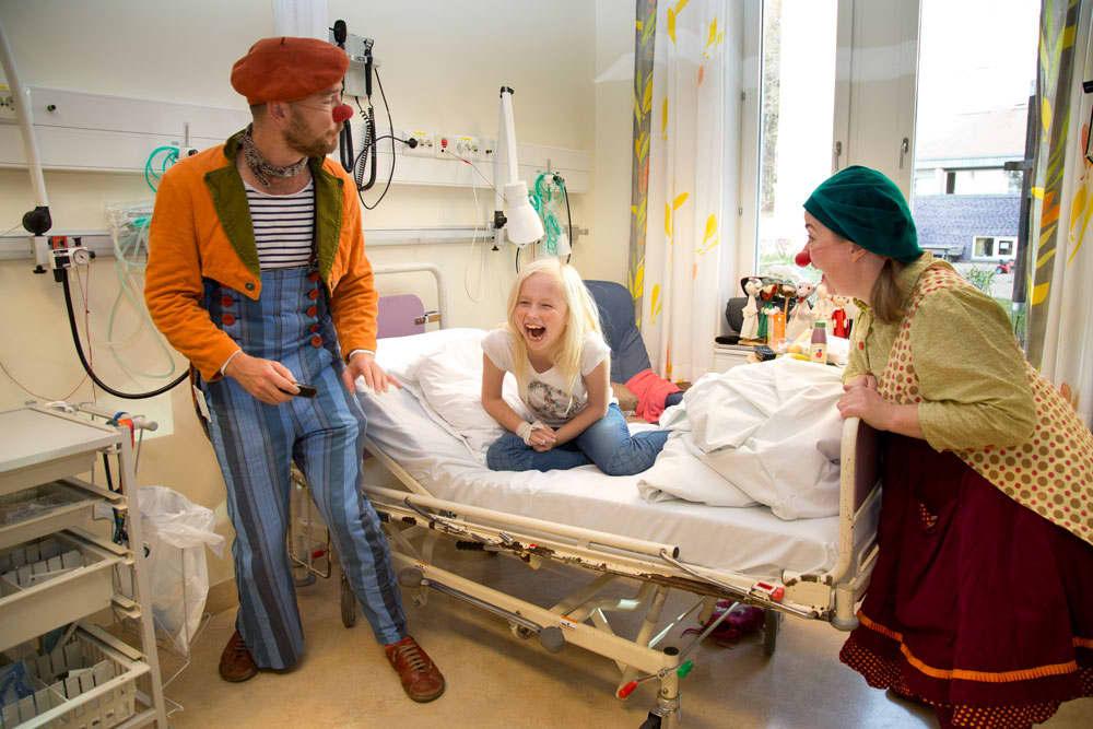 Sykehusklovnene får en ung sykehuspasient til å bryte ut i latter. Foto: Morten Eik.