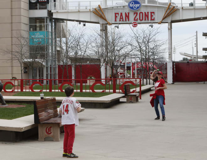 At left, Seneca Steinert (9) plays toss with his mother Anne Steinert, from Cincinnati, outside Great American Ball Park which would have been opening day with a game between the St. Louis Cardinals and the Cincinnati Reds.