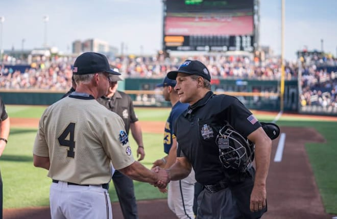 Tim Corbin greets an umpire at the 2019 College World Series.