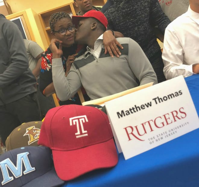 Thomas and his mother, Lyril, celebrate last week's signing