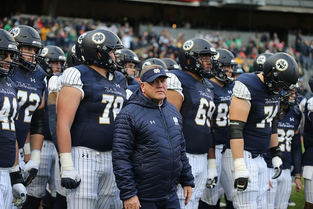 Guards Tommy Kraemer (78) and Aaron Banks (69) fittingly flank head coach Brian Kelly prior to last year's Syracuse game.