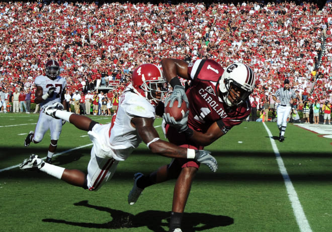 South Carolina receiver Alshon Jeffery evades a tackle from Alabama safety Mark Barron. Photo | Getty Images