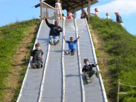 family members slide down a giant slide at Stokoe Farms in Rochester, NY