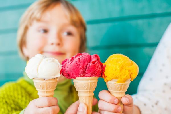 Child behind close up of three ice cream cones