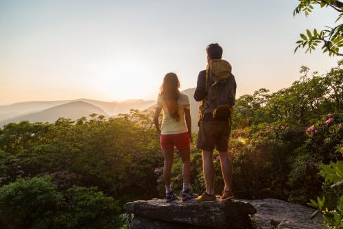 A couple watches the sun setting behind the western mountains from atop Craggy Gardens.