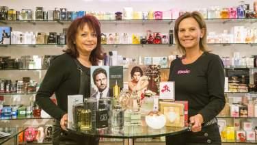 Two ladies presenting bottles of perfume