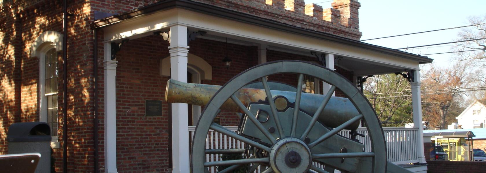 cannon in front of brick building