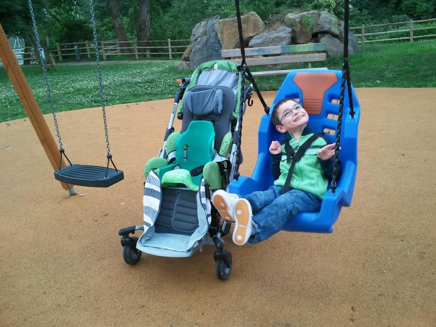 Child on a swing in a park, with a wheelchair next to them.
