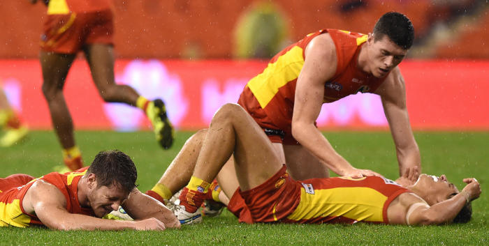 <em>Gold Coast Suns players Clay Cameron (l) and Sean Lemmens lie concussed after a collision during the AFL match between the Suns and Port Adelaide Power at Metricon Stadium on August 29, 2015. Picture: Dave Hunt/AAP</em>
